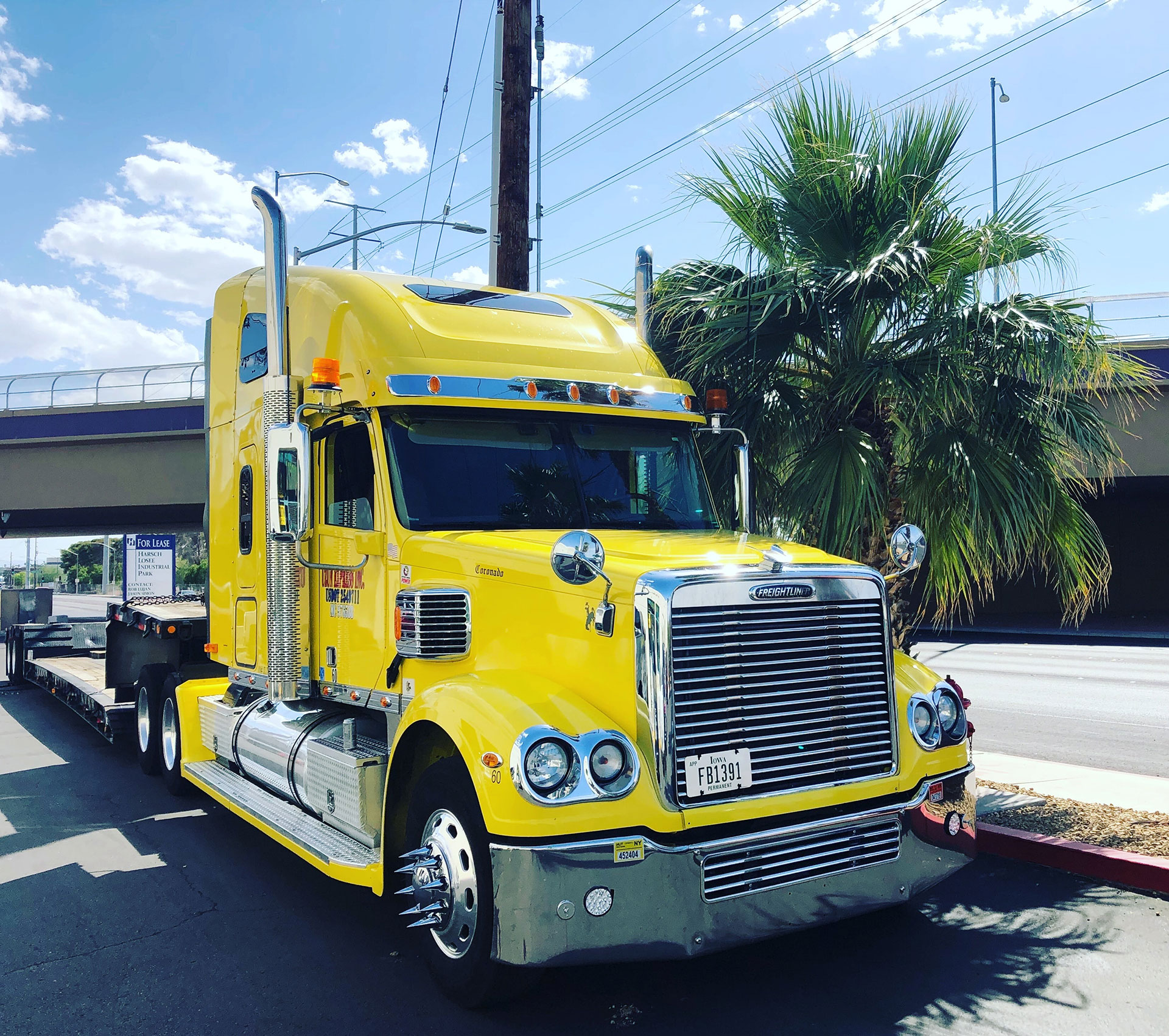 bright yellow semi-truck cab driving on road
