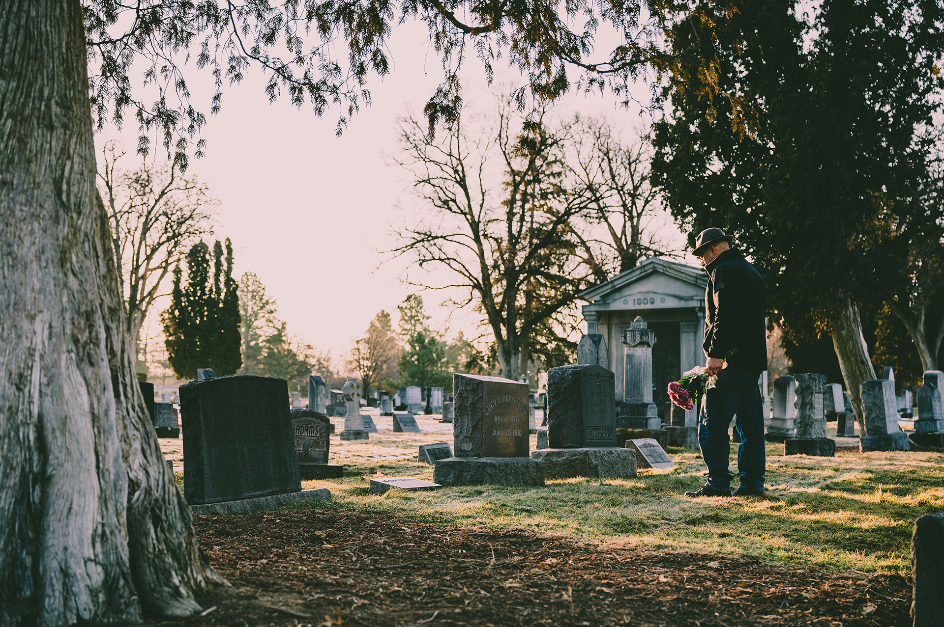 adult man standing in a cemetery holding flowers facing burial headstone