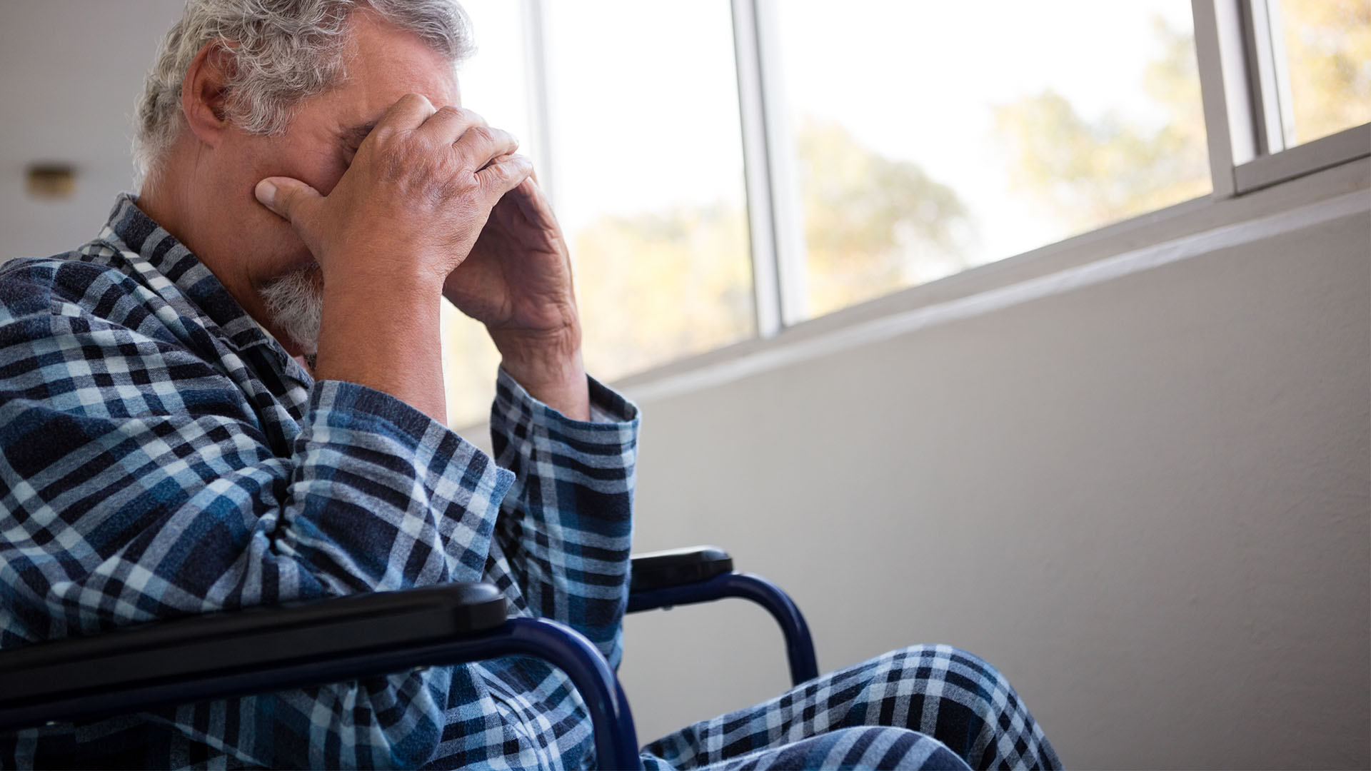 sad man in wheelchair with hands covering face