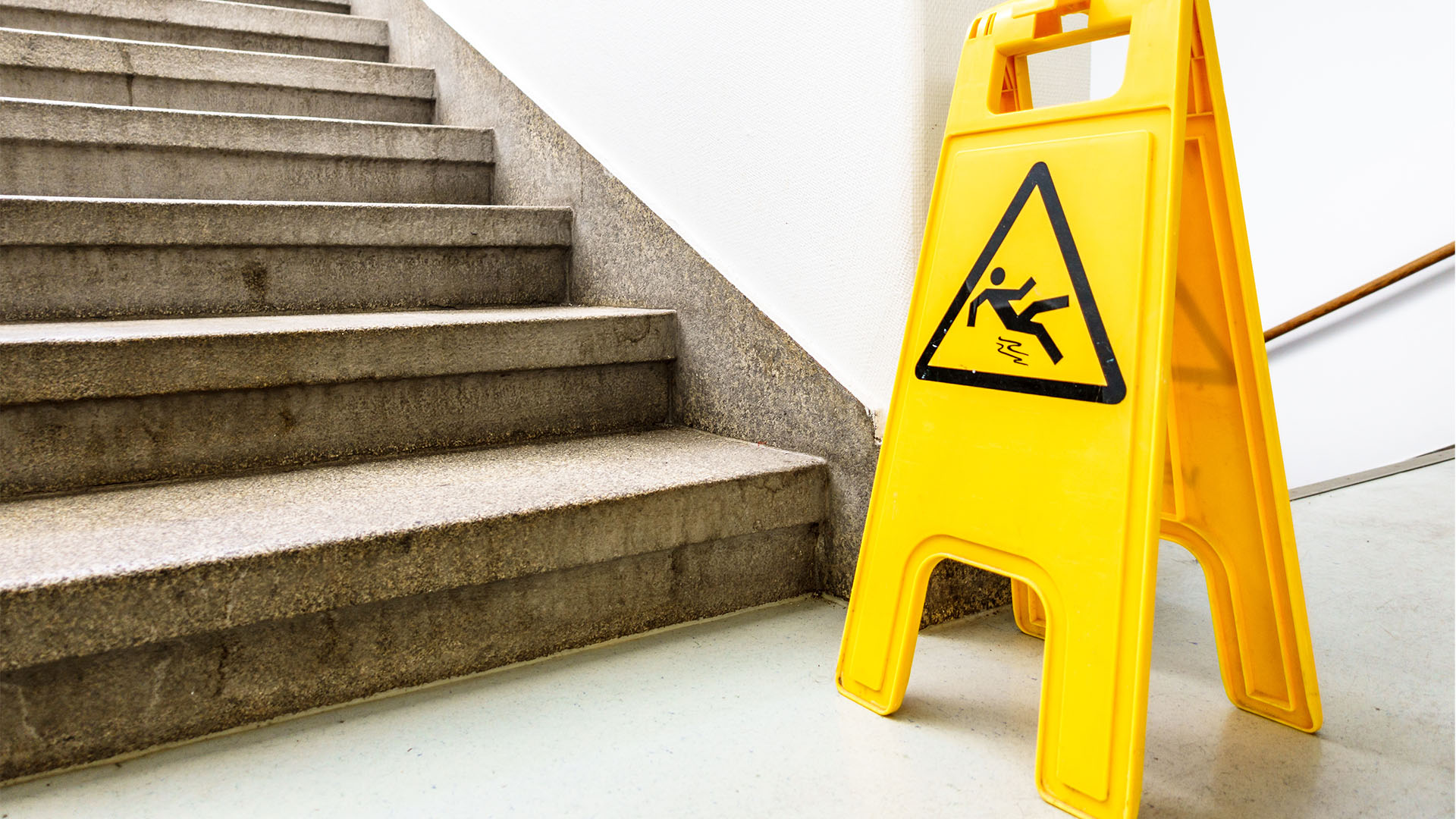 warning sign depicting a falling person placed at the bottom of staircase