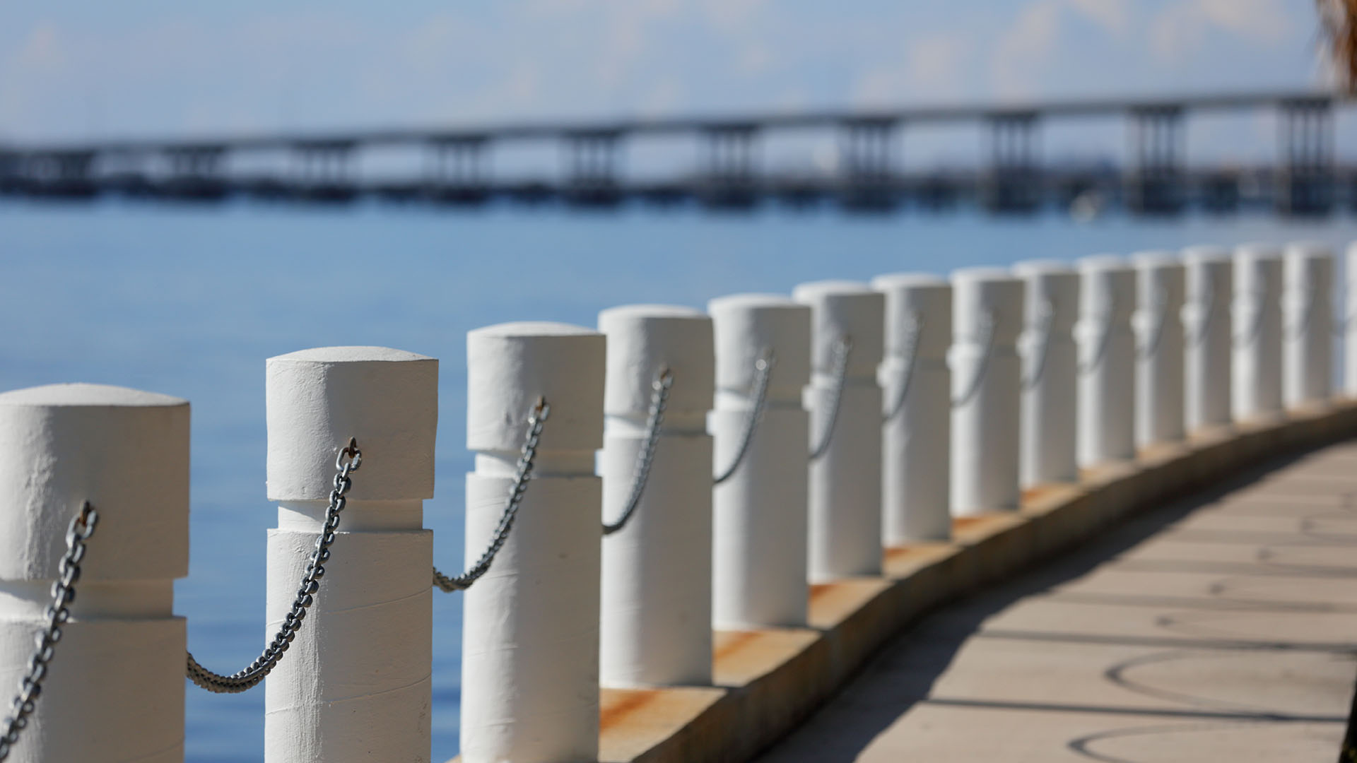 fence along the bay with bridge in background