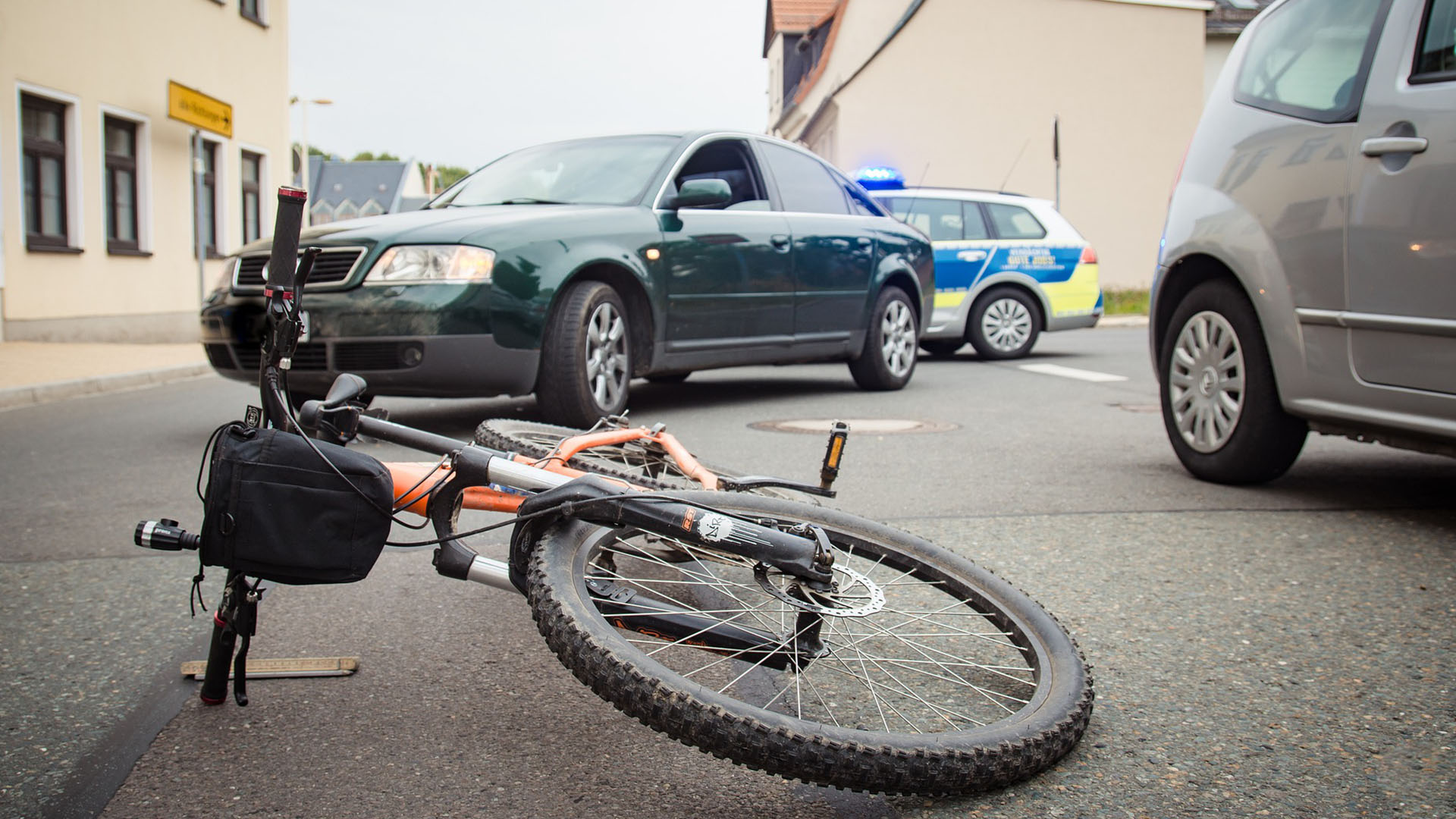 Bicycle Laying on Ground by Cars